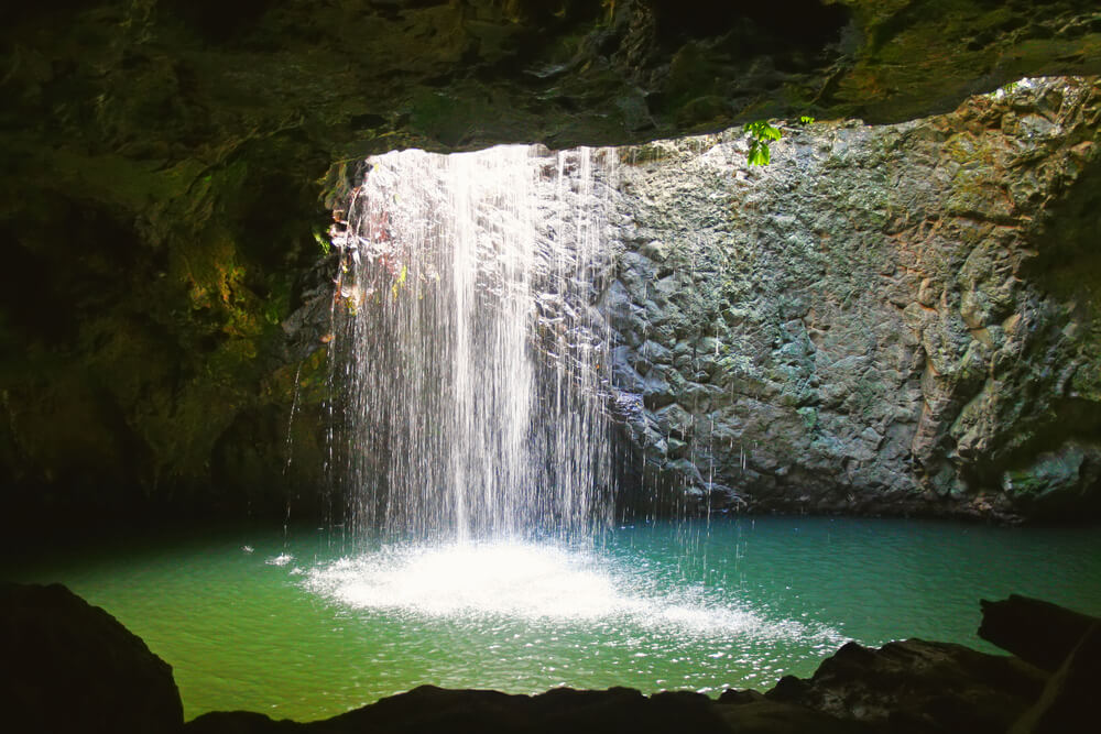 The waterfall at Natural Arch in Springbrook National Park in the Gold Coast hinterland in Queensland Australia.